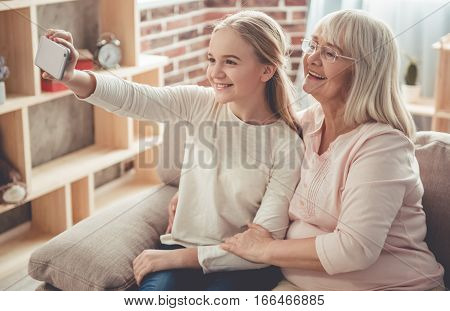 Beautiful granny and her granddaughter are doing selfie using a smart phone and smiling while sitting on couch at home