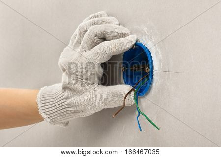 hand of electrician in glove installing plastic outlet box for electric wall sockets