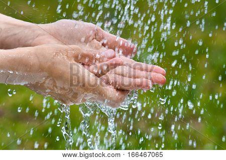 hands of woman under summer rain on blurred background