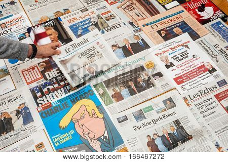 PARIS FRANCE - JAN 21 2017: Man holding Le Monde with America First above major international newspaper journalism featuring headlines with Donald Trump inauguration as the 45th President of the United States in Washington D.C