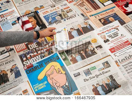 PARIS FRANCE - JAN 21 2017: Man holding lottery ticket abovemajor international newspaper journalism featuring headlines with Donald Trump inauguration as the 45th President of the United States in Washington D.C