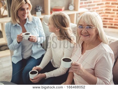 Three generations of women. Beautiful granny mother and daughter are drinking coffee talking and smiling while sitting on couch at home