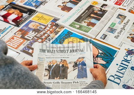 PARIS FRANCE - JAN 21 2017: Man holding The Wall Street Journal above major international newspaper journalism featuring headlines with Donald Trump Barack Obama Melania Trump and Michele Obama inauguration as the 45th President of the United States in Wa