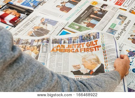 PARIS FRANCE - JAN 21 2017: Man readingmajor international newspaper journalism featuring news Donald Trump America First inauguration as the 45th President of the United States in Washington D.C and relatiosn with Vladimir Putin