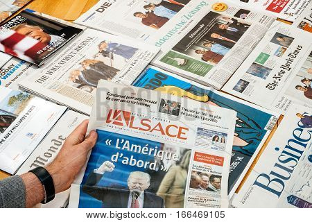 PARIS FRANCE - JAN 21 2017: Man holding L'Alsace above major international newspaper journalism featuring headlines with Donald Trump inauguration as the 45th President of the United States in Washington D.C