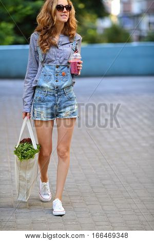 Woman in sunglasses with smoothie in disposable cup and fresh lettuce in linen bag in their hands on a city street