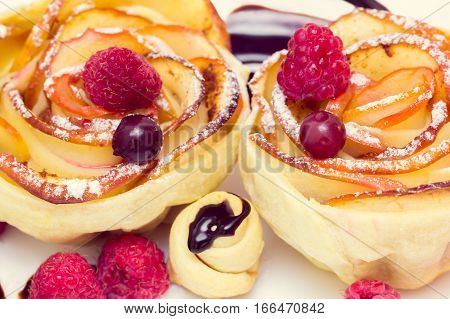 apple muffin with raspberry and blueberries on a white plate, drizzled with chocolate sauce