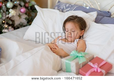 Child girl sleep in her bed near decorated Christmas tree in beautiful room in the holiday morning