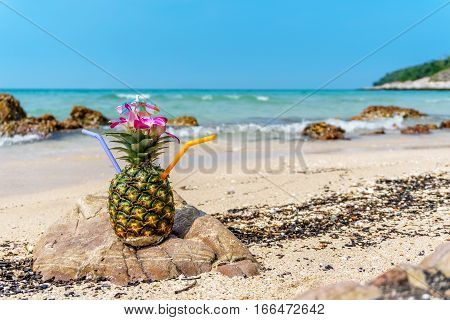 Tropical pineapple cocktail drink at the ocean beach