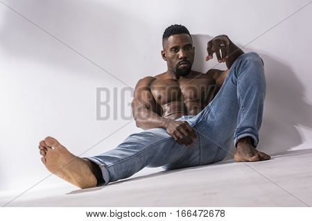 African American bodybuilder man, naked muscular torso, wearing jeans, sitting and leaning on white wall