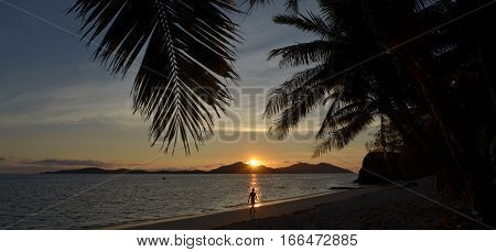 Person Walks On The Beach During Tropical Sunset