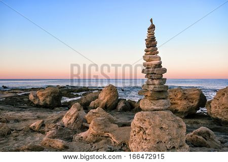 Cairn on the shore of the blue sea at dawn