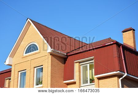 Attic roof exterior with asphalt shingles and plastic rain gutter system. Close up on Mansard house roofing type.