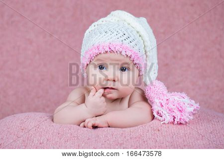 Beautiful little girl in pink warm headphones.