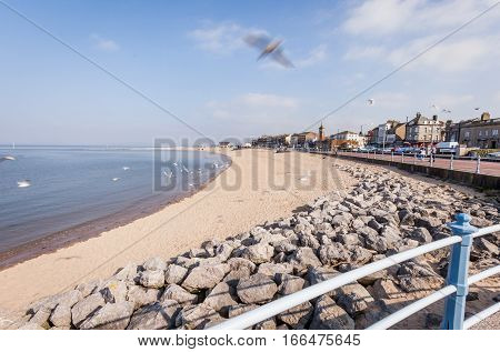 The empty sandy beach of the Lancashire seaside town of Morecambe on a bright Spring day.