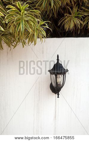 A black vintage lantern on a white fence wall with tree branches overhanging. Wall lantern. Outdoor lantern