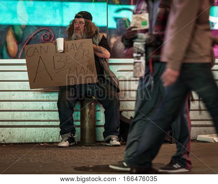 NEW YORK CITY USA - 19 APRIL 2011: A homeless character begging on the streets of NYC with a sign reading