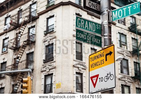 Street signs and architecture of Little Italy NYC USA on the corner of Mott St. and Grand St.