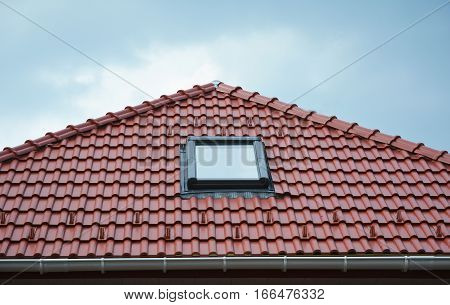 Close up on house roof window sun tunnel skylights or skylight after rain on red ceramic tiles roof. Attic skylight solution outdoor.