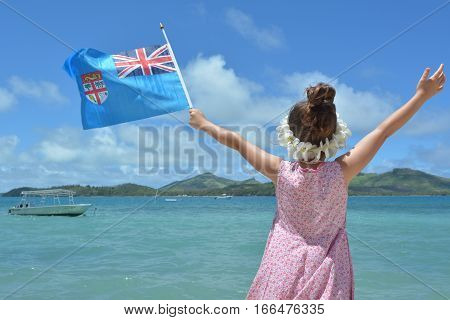 Young girl on family travel holiday vacation in Fiji waving the National flag of the Republic of Fiji. Real Peopla copy space