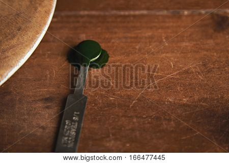 Close focus on small steel measure spoon ll with spirulina spice inside, isolated on side of rustic wooden table