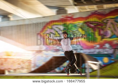 Young man is rollerblading. Rollerblader and graffiti. High speed and perfect balance.