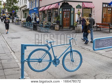 Reykjavik Iceland - July 8 2016: Shopping street Laugavegur in Reykjavik Iceland with people terrace and blue bicycle.