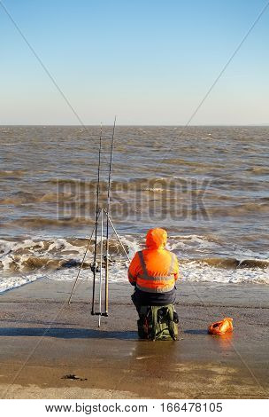 Penarth Vale of Glamorgan United Kingdom - January 22 2017: Angler fisherman sitting on the slipway in Penarth Cardiff in winter fishing in the Bristol Channel.