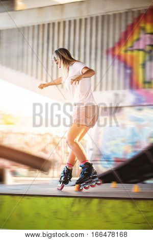 Girl on rollerblades. Young woman on blurred background. Ride with grace.