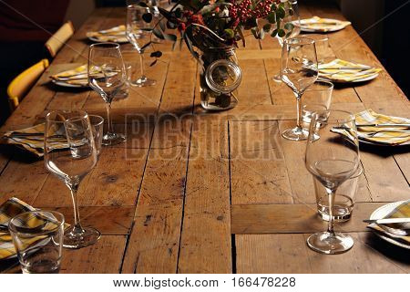 Beautifully served for holiday dinner table, between empty dishes and wine glasses and big jar with branches of eucalyptus and rowan inside in center, close shot