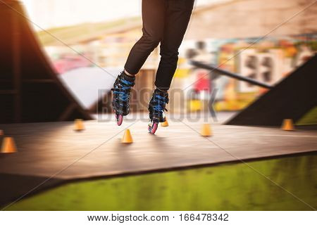 Legs on rollerblades. Orange slalom cones. Training in skatepark.