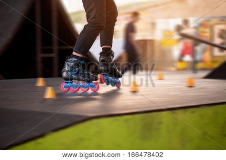 Legs of person rollerblading. Black skates with pink wheels. Be fast and agile.