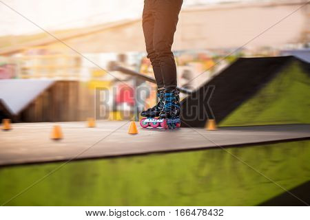 Legs of person on rollerblades. Rollerblader and slalom cone. Test your agility.