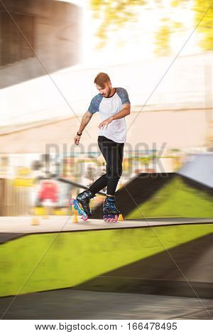 Young male on inline skates. Rollerblader beside slalom cones. Training of extreme sportsman.