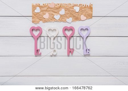 Key from love. Happy Valentines Day background with heart in keys form, greeting cards and paper letters, craft decorations, copy space on white wood planks