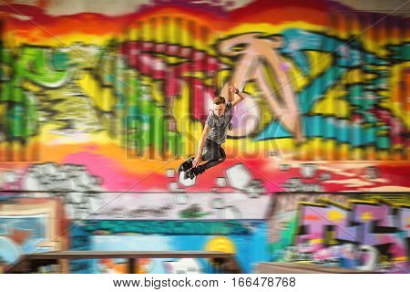 Guy on inline skates jumping. Inline skater on graffiti background. The brave genration.
