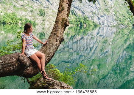 Young beautiful girl sitting on a tree on Obersee lake with clear green water and reflection Berchtesgaden National Park Bavaria Germany