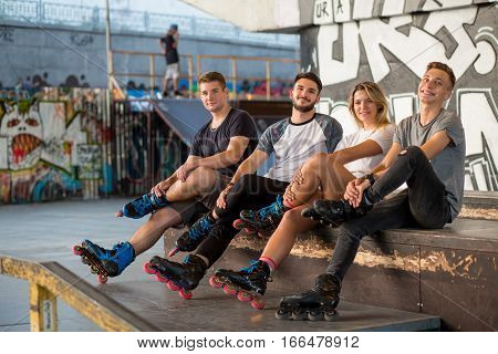 People on rollerblades sitting. Guys and girl in skatepark. Healthy and active youth.
