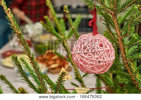 Christmas ball hanging on tree branch with people setting the festive table on the blurred background