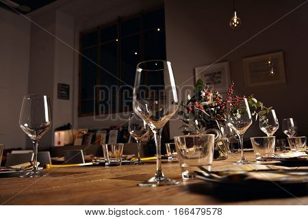 Close focus view on row of empty water and wine transparent glasses on served for holiday dinner table in big loft room at evening, low lightning