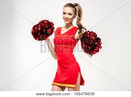 Blonde cheerleader posing with pom-poms and looking at camera on grey