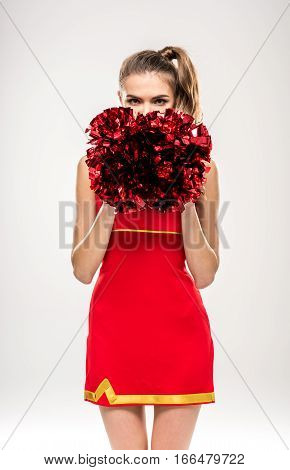 Beautiful cheerleader posing with pom-poms and looking at camera on grey