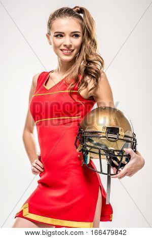 Beautiful blonde cheerleader posing with helmet on grey