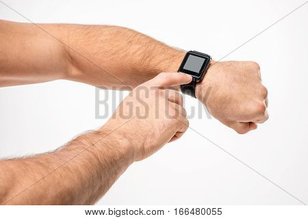 Partial view of man pointing on smartwatch