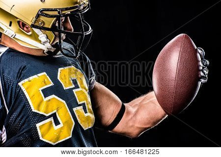 Muscular american football player in protective sportswear looking at ball