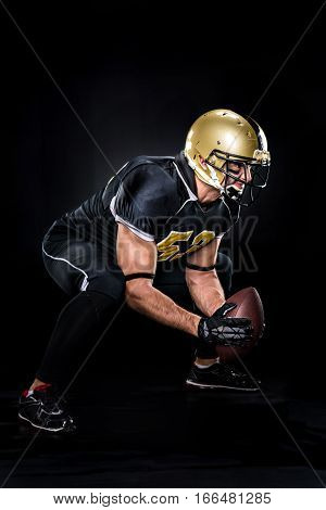American football player in uniform crouching on dark