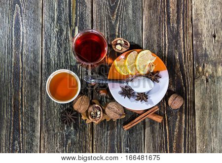 Mulled wine with honey cinnamon and lemon on a wooden table. Flat view.