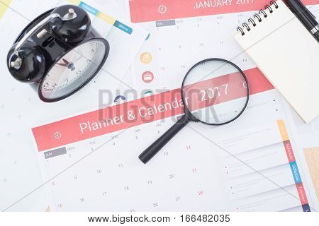 magnifier and business Calender Planner 2017 on desk office. organization management remind concept.