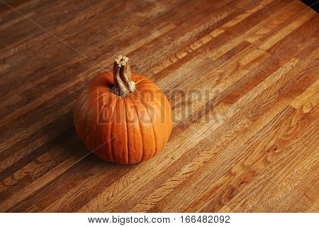 Orange fresh classic pumpkin isolated on rustic wooden table made from thin racks, top side view