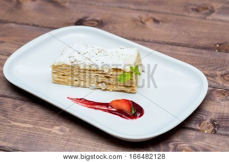 beautiful and delicious dessert millefeuille with berries on a white plate with sauce, beautiful restaurant supply